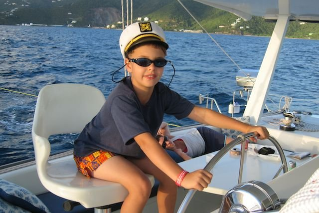 Child playing captain of the ship on a Virgin Islands Family Catamaran Charters