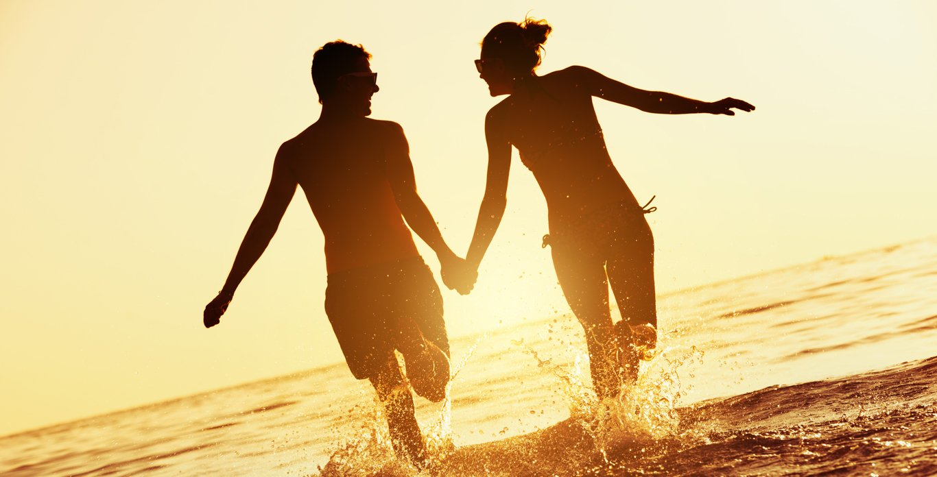 Newly Wedded Couple holding Hands on a Private Beach on Their Honeymoon Upscale Caribbean Private Yacht Charter