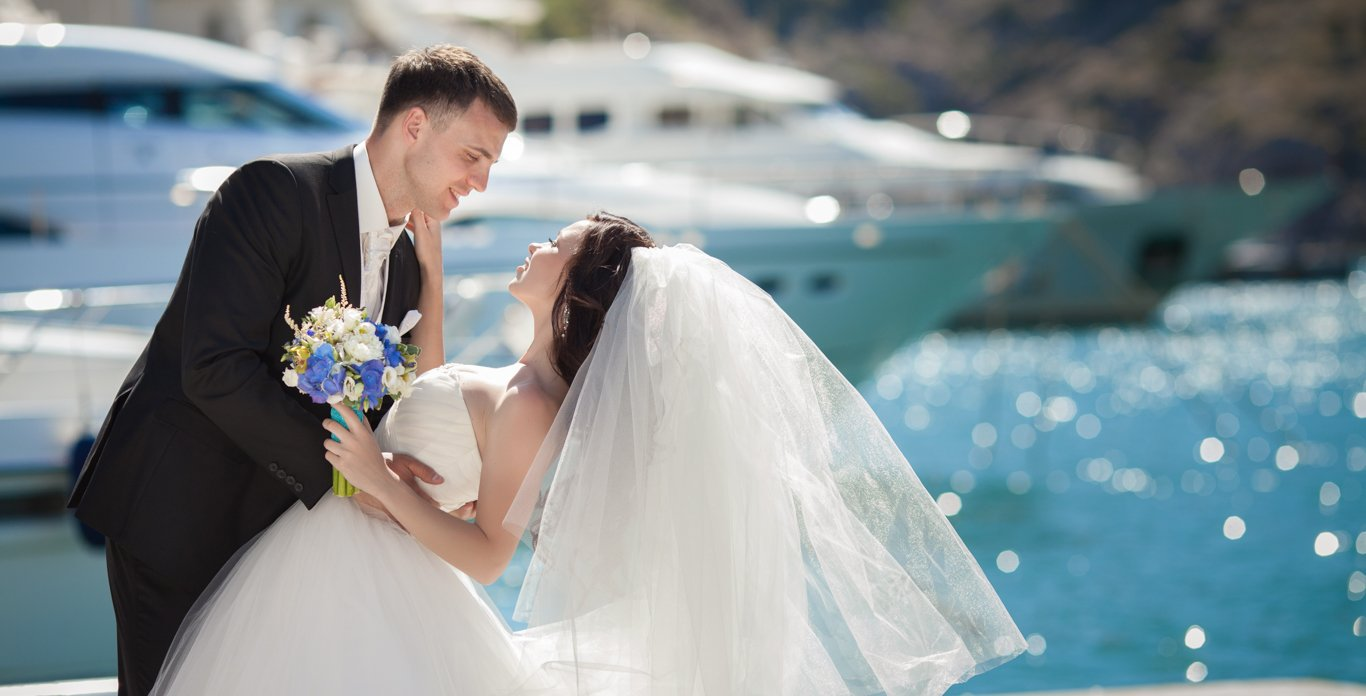 Happy wedded couple on board their luxury chartered yacht to celebrate their marriage.