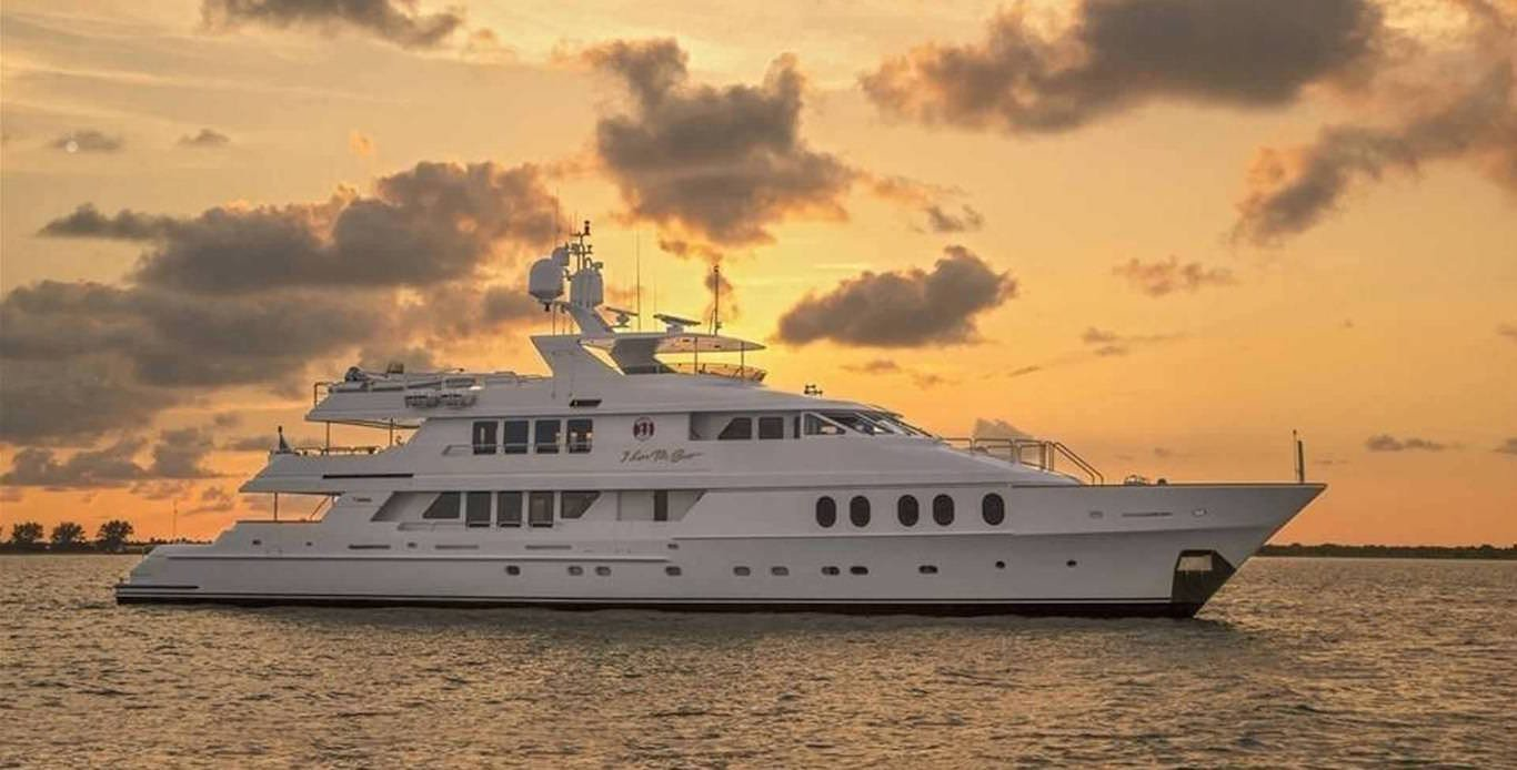 Caribbean Motor Yacht Charters anchored in harbor during sunset.