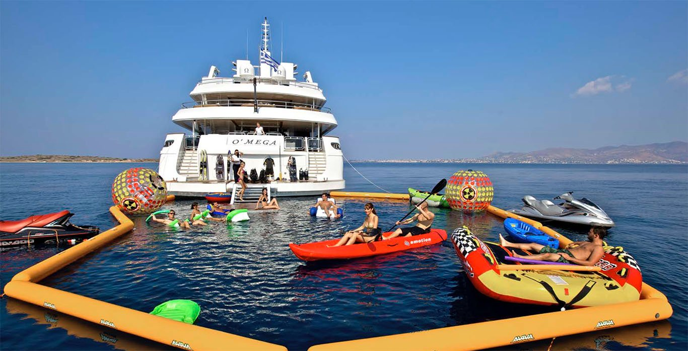 O'Mega Yacht Charter guests lounging in the water with a wide selection of water toys