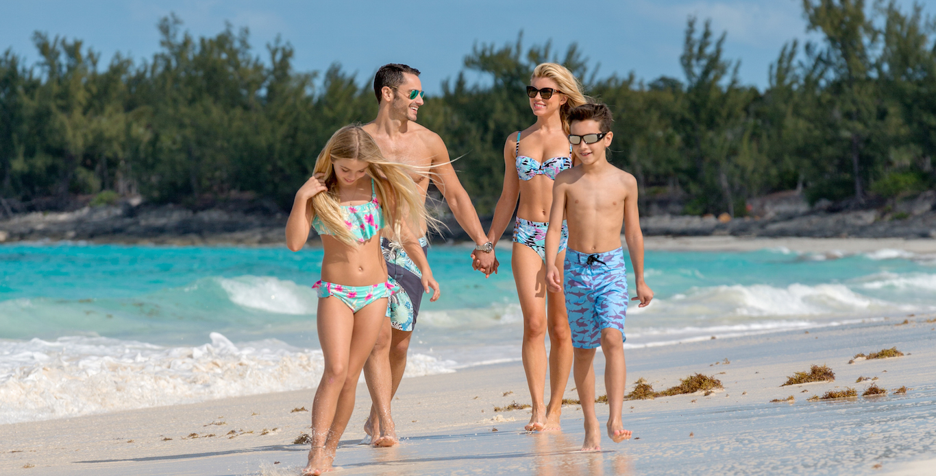 After sailing on their private catamaran yacht charter, a family of four is found strolling on on a secluded Caribbean beach.
