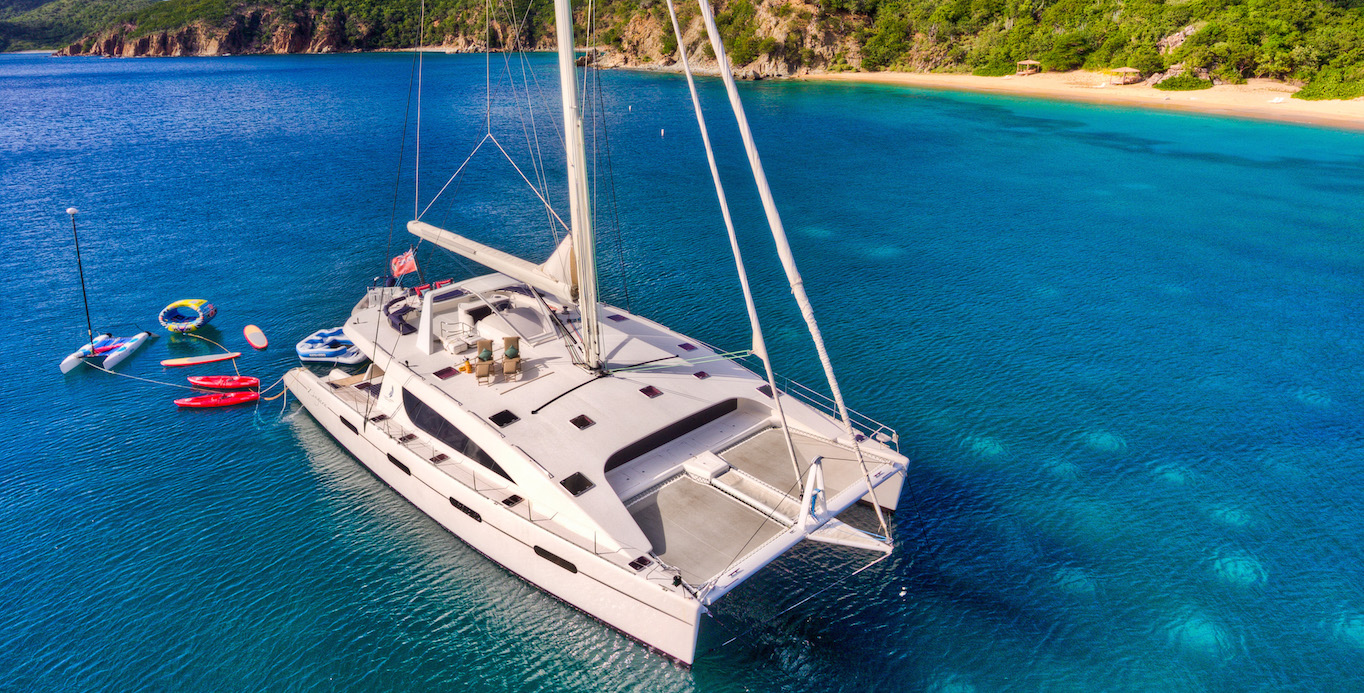 Arial View of a 10-person BVI Catamaran Charters with water toys off the bow.