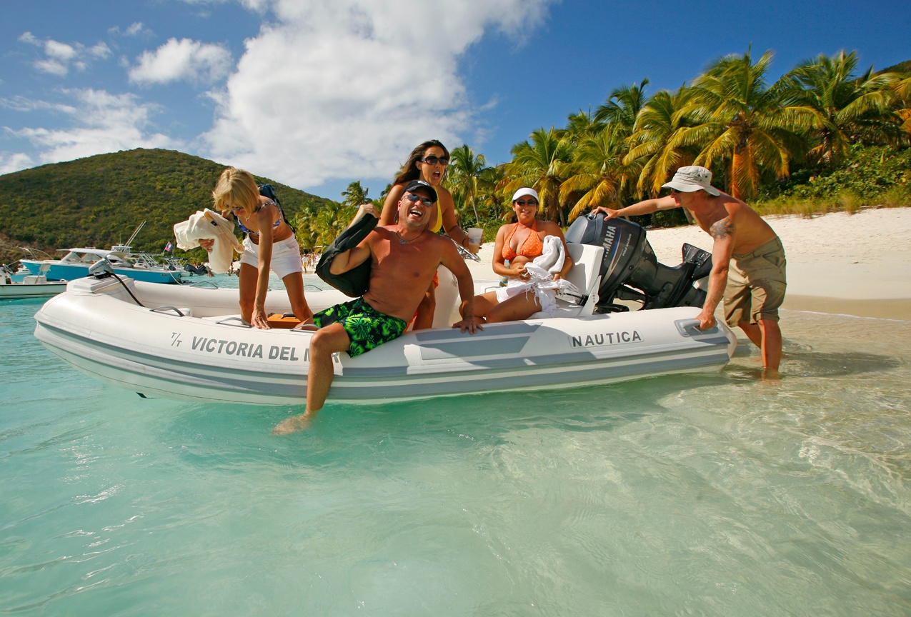 Picture of a group enjoying themselves on one of the water toys of a private luxury catamaran yacht charter.