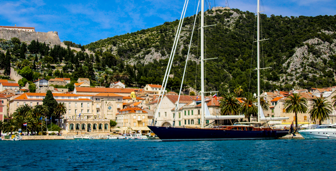Image of a luxury Hvar sailing yacht charter anchored in a harbor.